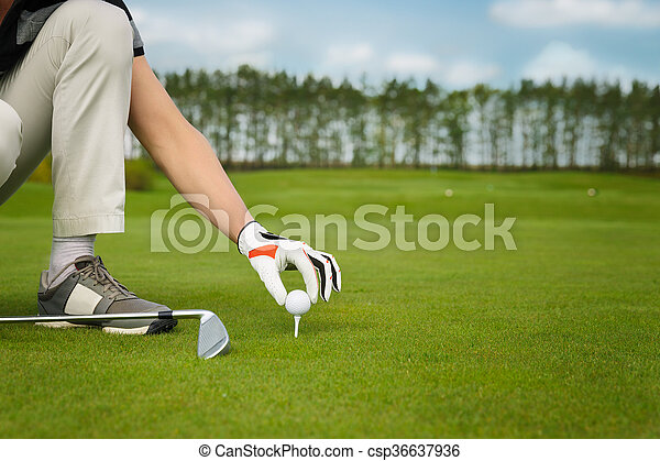 hand placing golf ball on tee - csp36637936