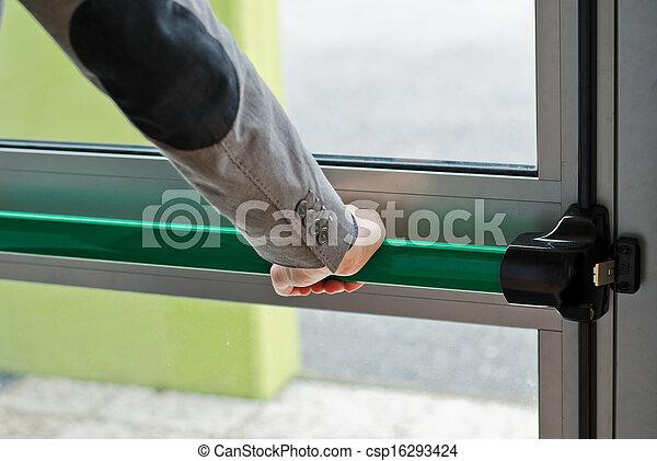 Hand pressing panic push bar to open door - csp16293424