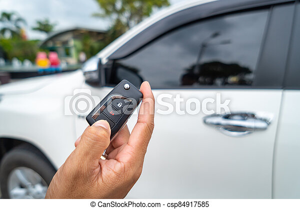 Hand pressing the button on the remote to lock or unlock the car with the remote control. - csp84917585
