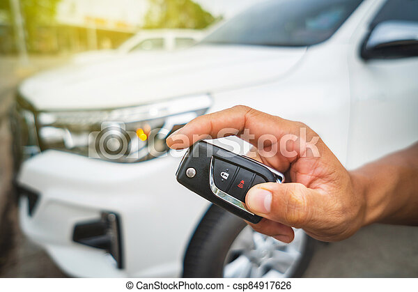 Hand pressing the button on the remote to lock or unlock the car with the remote control. - csp84917626