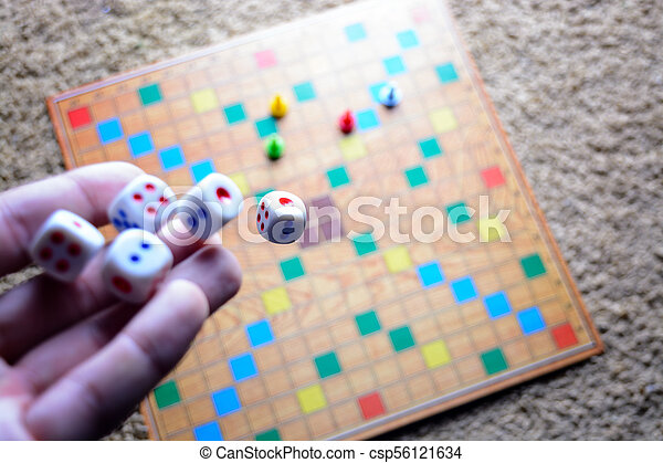 Hand throwing white dice background colorful blurred Board game. The dynamic moment of the game, selective focus. - csp56121634