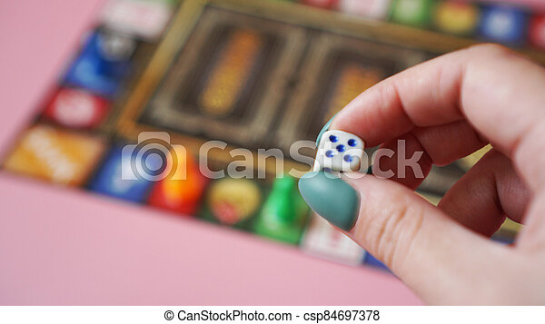 Hand throws the dice on the background of colorful blurred Board games - csp84697378
