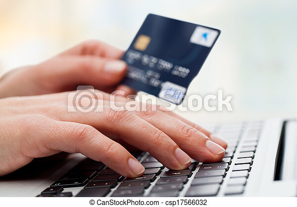 Hand typing on laptop with credit card. - csp17566032