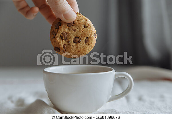 hand wants to dip brown cookies in a glass with coffee. - csp81896676