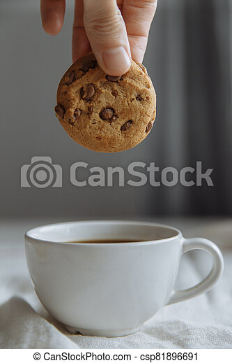hand wants to dip brown cookies in a glass with coffee. - csp81896691