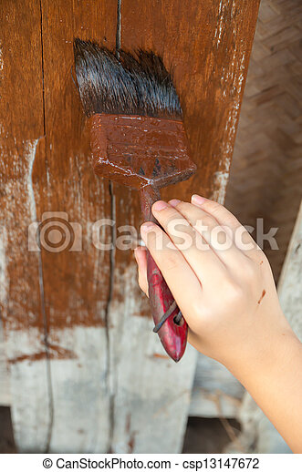 hand with a paint brush painting wooden wall - csp13147672