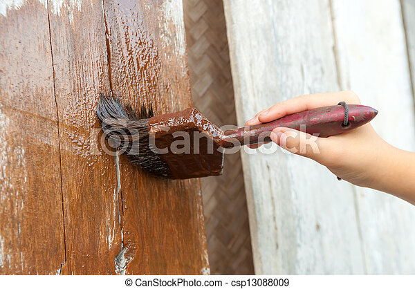 hand with a paint brush painting wooden wall - csp13088009