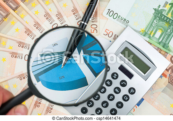 Hand with magnifying glass over a calculator - csp14641474