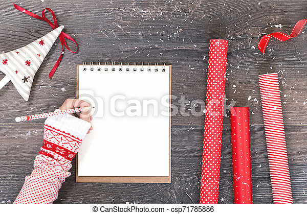 Hand with notepad Christmas tree and red gift wrapping paper - csp71785886