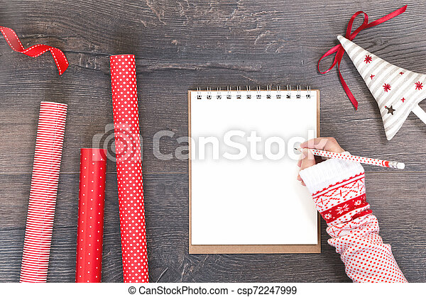 Hand with notepad Christmas tree and red gift wrapping paper - csp72247999