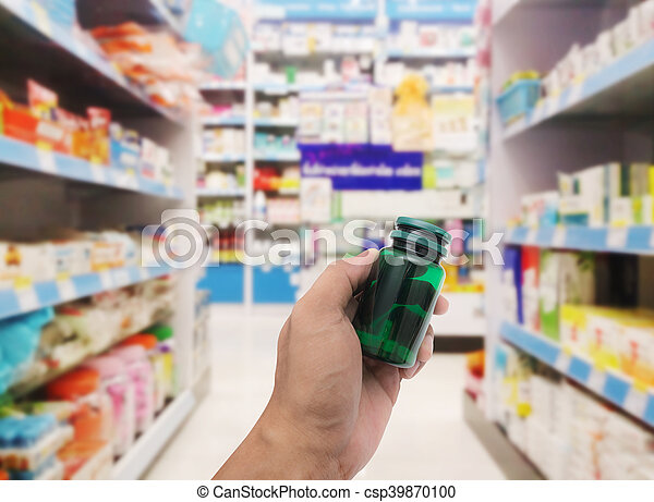 Hand With Plastic Pill Bottle On Pharmacy Store