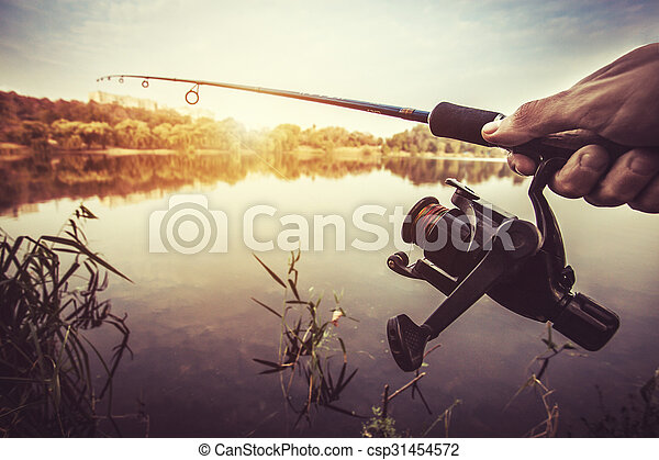 hand with spinning and reel on the evening summer lake - csp31454572
