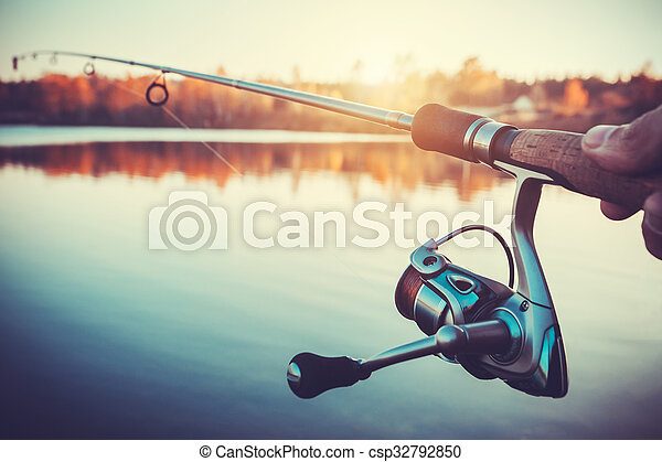 hand with spinning and reel on the evening summer lake - csp32792850