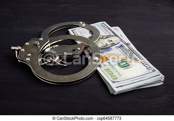 Handcuffs and money. Dollars for bail bonds. - csp64587773