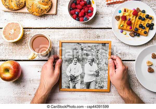 Hands holding picture of seniors, breakfest meal. Studio shot. - csp44391599
