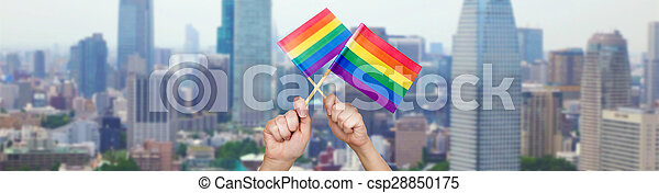 hands holding rainbow flags over city background - csp28850175