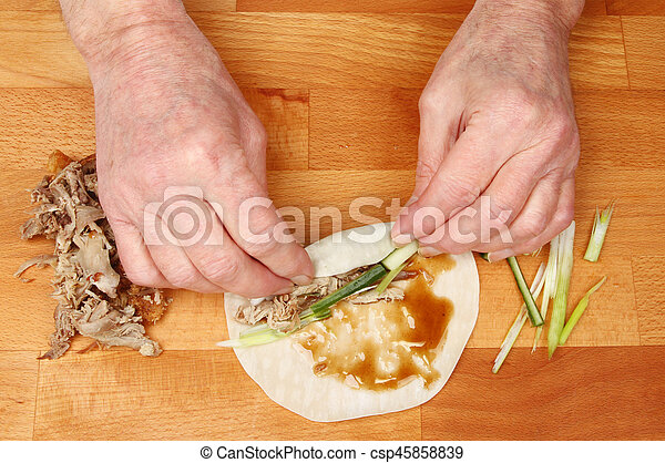 Hands making duck pancakes - csp45858839