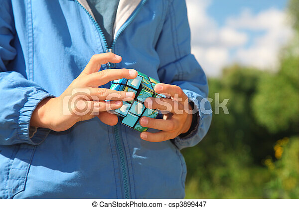 hands of boy  with magic cube outdoor in summer - csp3899447