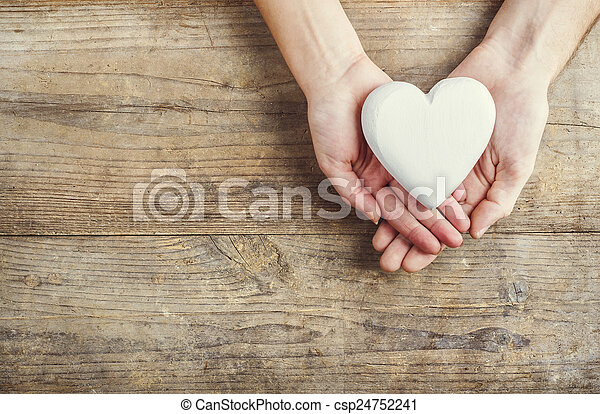 Hands of man and woman holding a heart together. - csp24752241