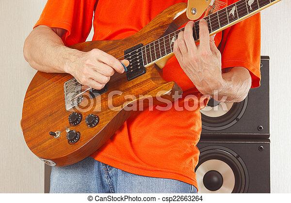 Hands of man put guitar chords closeup.