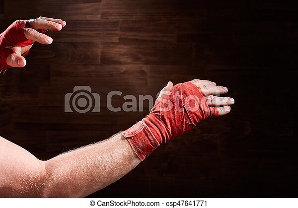 Hands of muscular athletic man with red bandage against brown ...