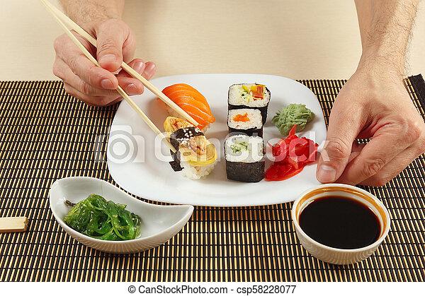 Hands Taking Sushi With Chopsticks Sushi Set Hiyashi Wakame Salad And Soy Sauce On Bamboo Mat