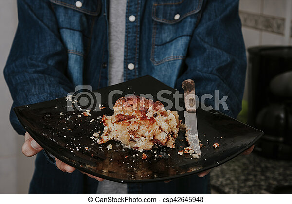 hands with the plate of cake in the apartment - csp42645948
