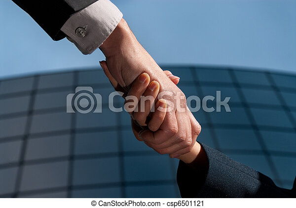 Handshake unrecognizable business man and woman on modern building background - csp6501121