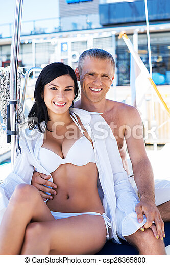 cdc1c66c0e Handsome and rich man and a beautiful and sexy woman in swimsuit relaxing  on a sailing