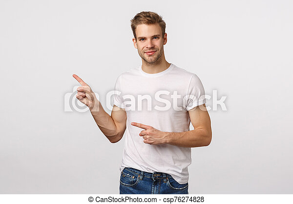 Handsome, assertive pleased young blond man with bristle, pointing upper left corner, smiling as looking partner, discuss business concepts, suggest product, recommend place, white background - csp76274828