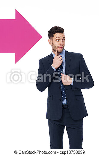 Handsome businessman looking in the direction in which the arrow showing  - csp13753239