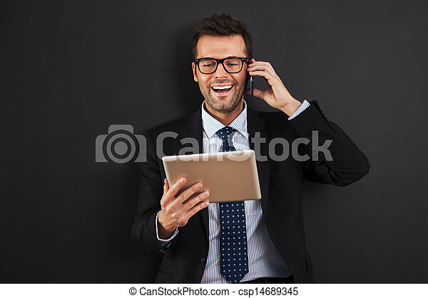 Handsome businessman working with mobile phone and digital tablet - csp14689345