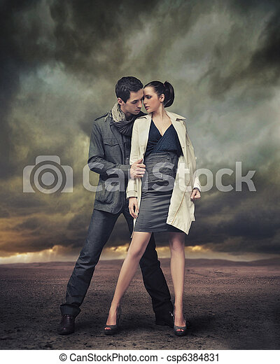 Handsome couple posing over stormy background - csp6384831