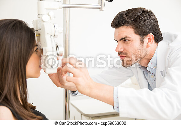 3803817e681 Handsome Doctor Doing Eyesight Measurement To Young Woman With Optical  Phoropter