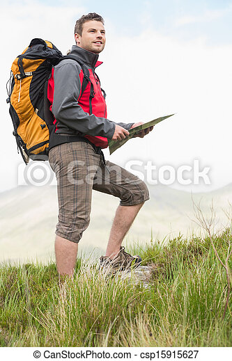Handsome hiker with rucksack walking uphill holding a map - csp15915627