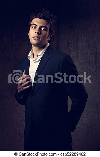 db2f8f68 Handsome Male Model Posing In Fashion Suit And White Style Shirt Looking On Dark  Shadow Background.