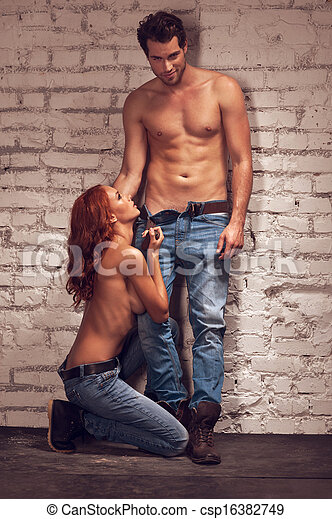 Handsome male model posing with beautiful girl on sexy shoot. Standing nude and looking brutal  - csp16382749