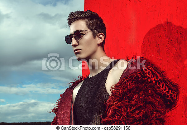 Fashion Shot Of A Professional Handsome Male Model In Long Red Fur Coat Posing In A Wheat Field