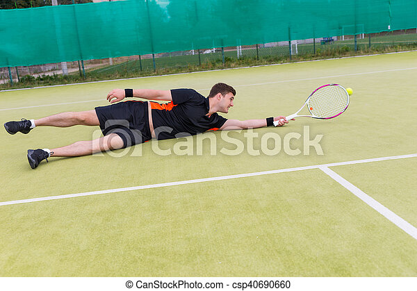 Handsome male tennis player in action during the game fallen on a court - csp40690660