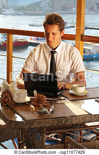 Handsome man businessman work at the laptop in restaurant - csp11077429