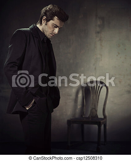 Handsome man in a business suit on a dark background - csp12508310