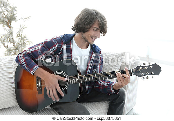 Handsome man playing on the guitar on the couch at home - csp58875851