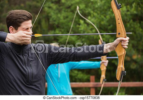 Handsome man practicing archery - csp15770838