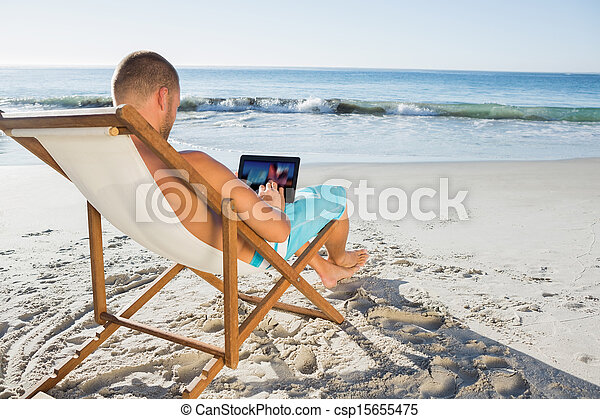 Handsome man scrolling on his tablet pc - csp15655475