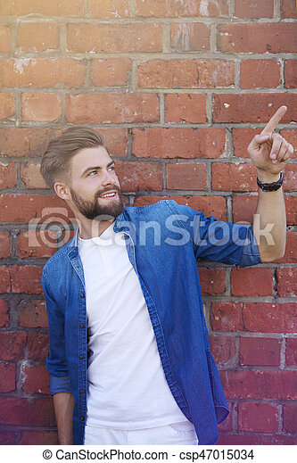 Handsome man showing on brick wall - csp47015034