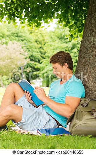 Handsome man student in a city park on summer day  - csp20448655