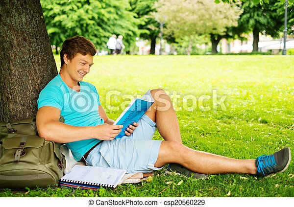 Handsome man student in a city park on summer day  - csp20560229