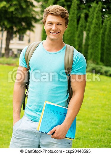 Handsome man student in a city park on summer day  - csp20448595