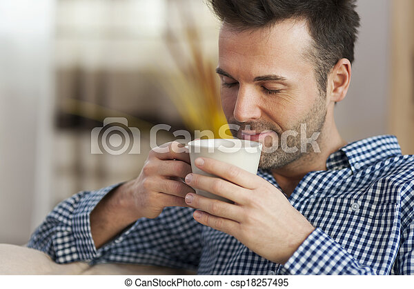 Handsome man tasting morning coffee 