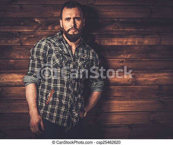 Handsome man wearing checkered  shirt in wooden rural house interior  - csp25462620